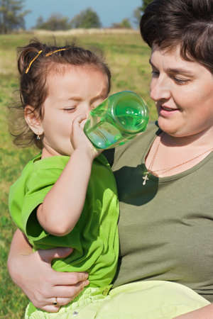 Little girl drinking water and her mother is watching Stock Photo