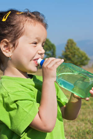 Happy little girl drinking fresh water Stock Photo