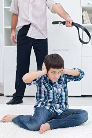 Strict father punishing his son photo