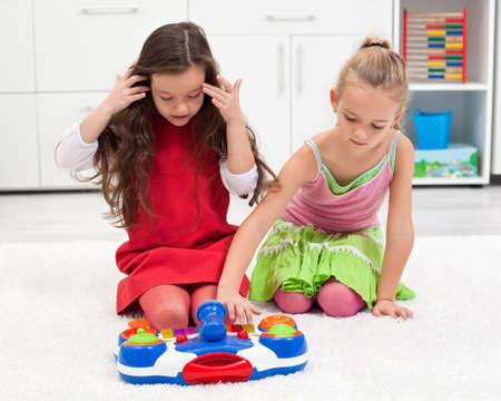 Beautiful little girls playing on the carpet Stock Photo - 18061159
