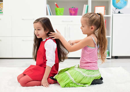 Happy little girl combing her girlfriends hair Stock Photo