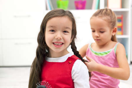 Happy little girl smiling while her girlfriend braiding plait  Stock Photo
