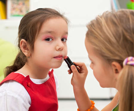 Little girl applying lipstick on her girlfriends mouth Stock Photo