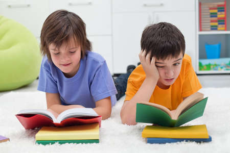 Two little boys with books, the one reading with  interest and the other boring