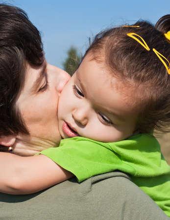 Little girl resting on her mothers shoulder