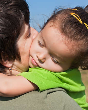 Little girl with closed eyes resting on her mothers shoulder Stock Photo