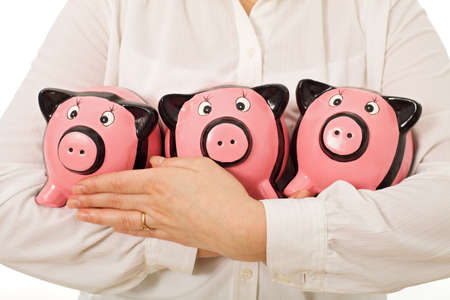 Businesswoman holding three piggy-banks
