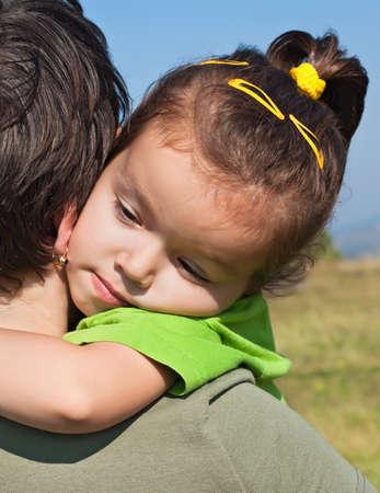 Happy little girl resting on her mothers shoulder