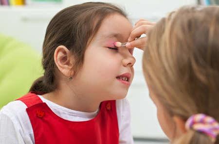 Little girl doing make-up to her girlfriend