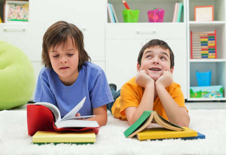 Two little boys with books, the one reading with  interest and the other dreaming looking up near the books Stock Photo