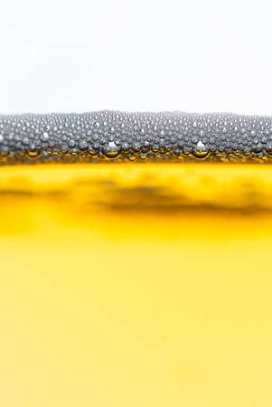 Fresh beer with froth and condensed water pearls on white  background photo