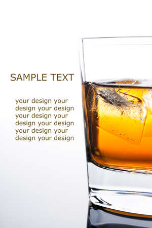 scotch whisky: glass of whiskey with ice cubes on white background