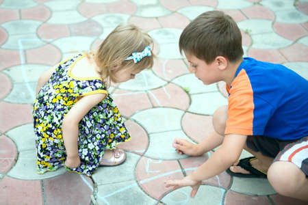 Two children drawing by chalk on a sidewalk photo
