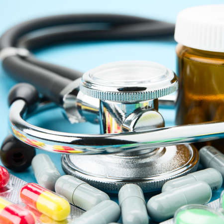Pills and stethoscope on blue bacground photo