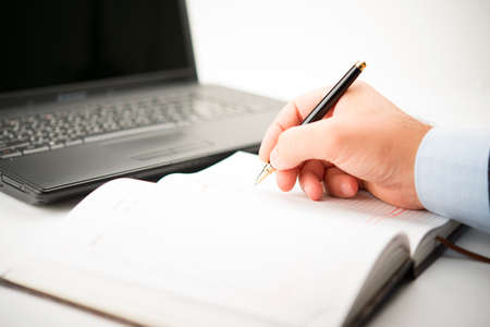 write writing: Businessman taking notes and planning in a meeting