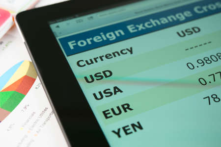 nyse: Modern tablet pc on a table with currency exchange information Stock Photo