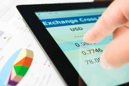 forex: Hand on screen tablet pc with currency exchange information Stock Photo