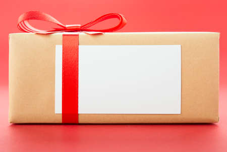 Wrapped gift box with red bow, isolated on red background Stock Photo - 16409738