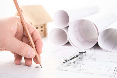 architect hand with pencil drawing blueprints Stock Photo