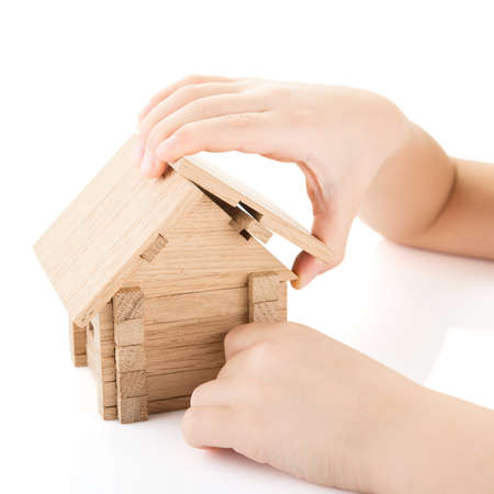 Child hands build a wooden house photo