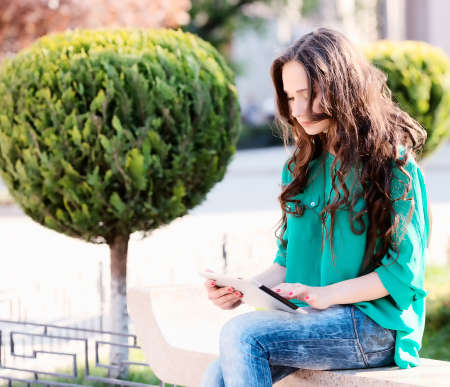 Young woman using tablet pc. Outdoor shoot photo