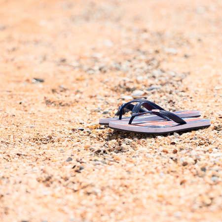 Blue slippers on the sandy beach . photo