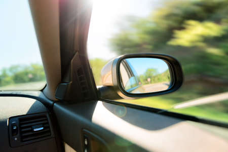 the car window: Shoot in rear-view mirror of car .