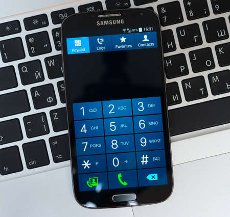samsung galaxy: SIMFEROPOL, RUSSIA - NOVEMBER 01, 2014:  Keypad of Samsung Galaxy S4 over Apple Macbook Pro keyboard. Samsung Galaxy S4 is an Android smartphone produced by Samsung Electronics. Editorial