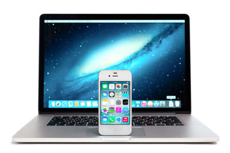 81: SIMFEROPOL, RUSSIA - NOVEMBER 01, 2014: Apple iPhone stay over Macbook and displaying iOS 8.1 homescreen. iOS 8.1 operating system designed by Apple Inc. Official release of October 20, 2014