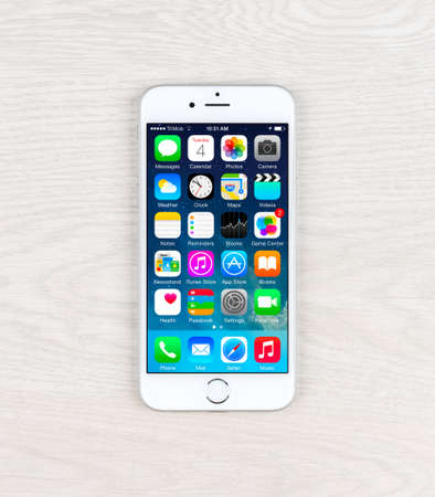81: SIMFEROPOL, RUSSIA - NOVEMBER 03, 2014: Apple iPhone 6 over table displaying iOS 8.1 homescreen. iOS 8 is the eighth major release of the iOS mobile operating system designed by Apple Inc. Editorial