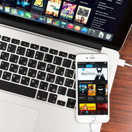 SIMFEROPOL, RUSSIA - NOVEMBER 03, 2014:  iTunes application on Apple iPhone 6 display over Macbook keyboard. iTunes is a media player and media library, developed by Apple Inc.