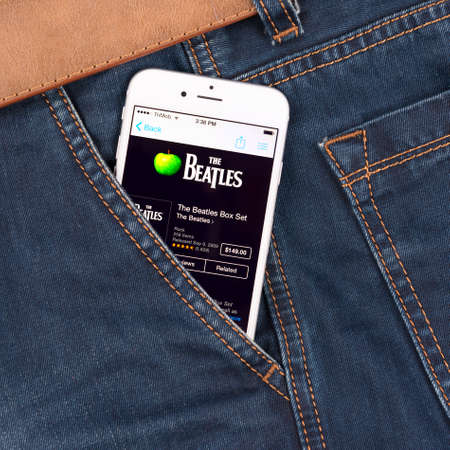 john lennon: SIMFEROPOL, RUSSIA - NOVEMBER 11, 2014: Apple iPhone 6 in jeans pocket displaying Beatles band music in iTunes. The Beatles were an English rock band that formed in Liverpool, in 1960.
