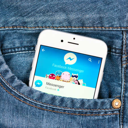 microblogging: SIMFEROPOL, RUSSIA - NOVEMBER 11, 2014: Silver Apple iphone 6 in pocket displaying facebook messenger app. Facebook Messenger is an messaging service which provides text and voice communication