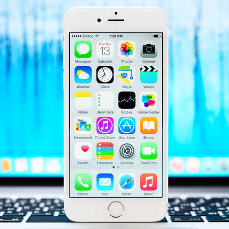 81: SIMFEROPOL, RUSSIA - NOVEMBER 13, 2014: Apple iPhone 6 stay over Macbook and displaying iOS 8.1 homescreen. iOS 8 is the eighth major release of the iOS mobile operating system designed by Apple Inc.