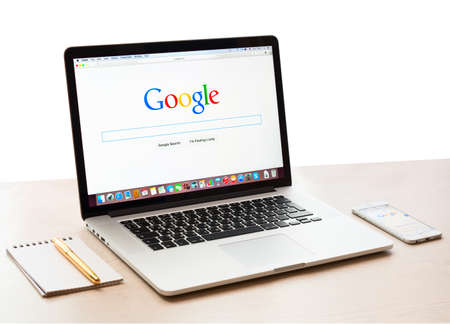 google: SIMFEROPOL, RUSSIA - NOVEMBER 16, 2014:  Google webpage on Macbook pro and iPhone 6 display. Google is an American multinational corporation specializing in Internet related services and products Editorial
