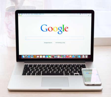 manzana: Simferopol, RUSIA - 16 noviembre 2014: la página web de Google en MacBook Pro y iPhone 6 pantalla. Google es una empresa multinacional estadounidense que se especializa en servicios y productos relacionados con Internet
