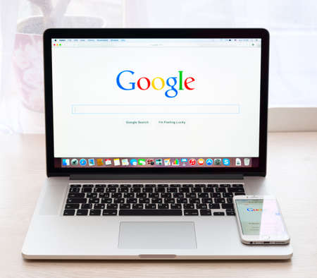 SIMFEROPOL, RUSSIA - NOVEMBER 16, 2014:  Google webpage on Macbook pro and iPhone 6 display. Google is an American multinational corporation specializing in Internet related services and products Editorial