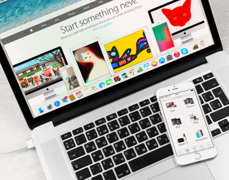 electronics store: SIMFEROPOL, RUSSIA - JANUARY 10, 2015: Apple Store application on Apple iPhone 6 display over Macbook keyboard. The Apple Store is the online store of Apple Inc.