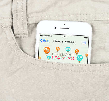 lifelong: Simferopol, Russia - April 18, 2015: White Apple iPhone 6 in the pocket, displaying applications for lifelong learning in the Apple store. Editorial