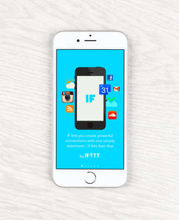 mobile app: Moscow, Russia - May 25, 2015: Apple iPhone 6 over table displaying IFTTT application. IFTTT is a web-based service that allows users to create chains of simple conditional statements, Editorial