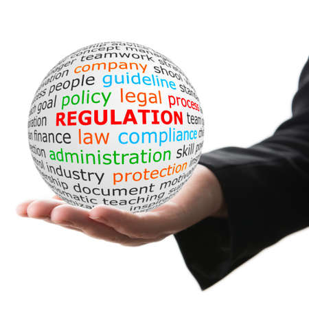 regulation: Regulation concept. Hand take white ball with red inscription regulation . Stock Photo