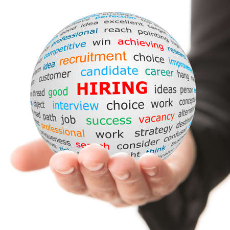 Hiring concept. Hand take white ball with wordcloud and hiring word in red color. Stock Photo