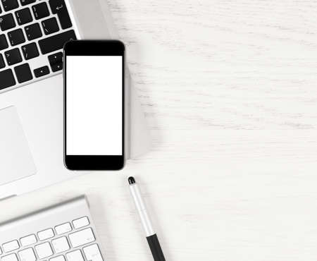 Top view: Black smartphone with blank screen lying over silver laptop on white table. Stock Photo