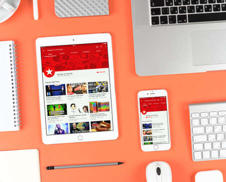 Moscow, Russia - October 13, 2016: Top view on workplace. Iphone and ipad over red background displaying Youtube app. YouTube is the popular online video-sharing website, founded in February 14, 2005 Editorial