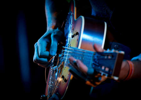 Dobro guitar with hands while playing in live concert, blue, brown colors