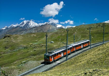Gornergratbahn train in Switzerland Alps is climbing from Zermatt to Gornergrat