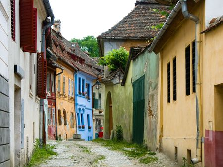 Old medieval street view with houses in Sighisoara, saxon city in Transylvania, Romania Imagens