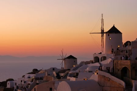 Oia sunset, in Santorini island (Greece). The tourists from all island of Thira (Santorini, Cyclades) come daily for the sunset, the most beautiful from Cyclades