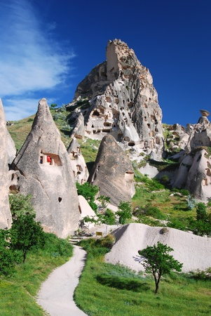 Uchisar is the tallest village in Cappadocia, visible for a great distance from the region's other towns such as Urgup and Avanos. The natural fortress of Uchisar, riddled with man made dwellings and dovecotes, dominates the skyline of Cappadocia. Stockfoto
