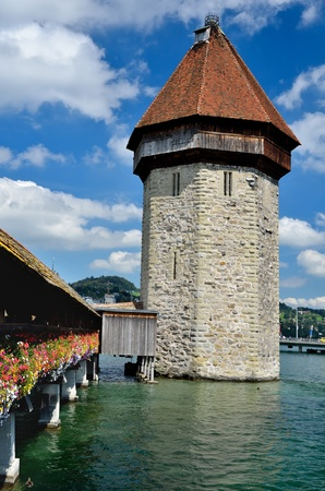A view of the famous wooden Chapel Bridge of Luzern in Switzerland, with the tower in foreground photo